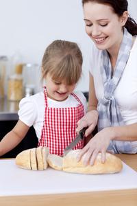 Frau und Kind schneiden Brot